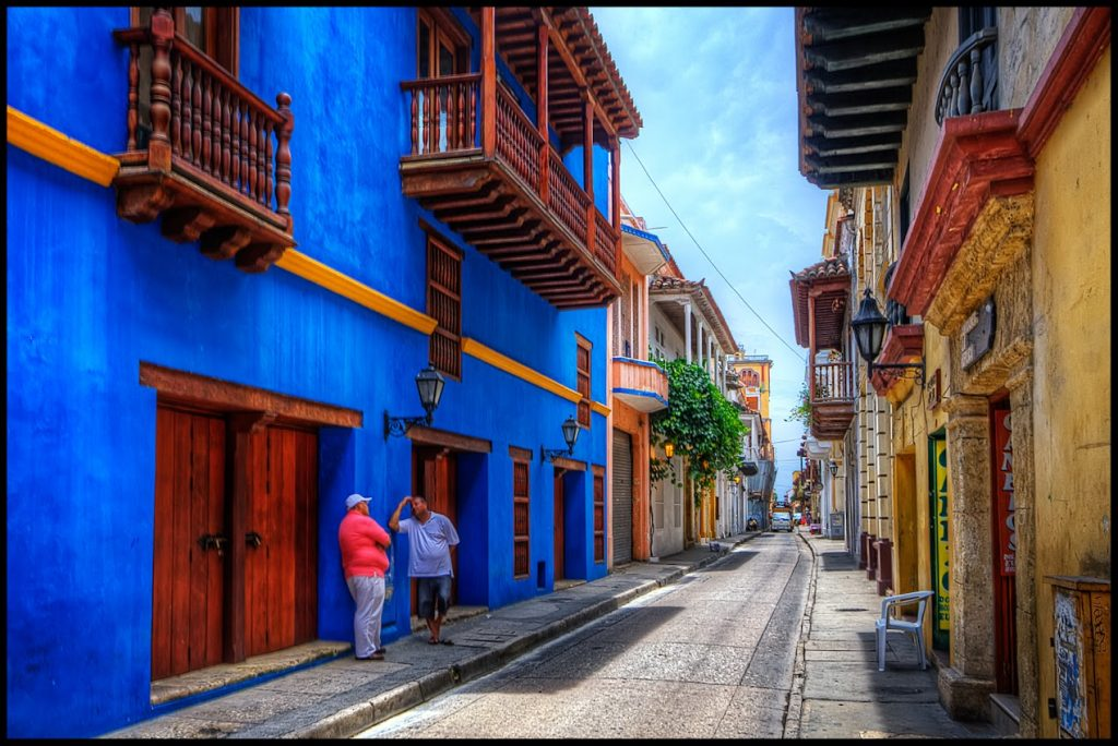 All the streets around old-town Cartagena look like this. The colors vary, but they are often strong, and lots of nice balconies.HDR of 3 handheld shots. This time Photomatix was not able to crisply align the images, but I insisted in using it because it is the only shot Ihave of this nice blue building. Cranked up the smart sharpen to make up the fuzziness, used Freaky Detail again (http://www.scottkelby.com/blog/2010/archives/8691), which is similar to Nik Tonal Contrast. For scenes with walls like these I prefer freaky detail because Tonal Contrast enhances the roughness of the walls too much. I masked the sky and street when applying freaky detail. Some dodging on the shadowed walls, and then Nik Skylight filter to give it a more sunny look.